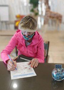 Woman in pink jacket working on paperwork.
